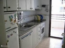 Keuken compleet ingericht met elektrisch fornuis, oven, vaatwasser, magnetron, en toegang naar terras 2.