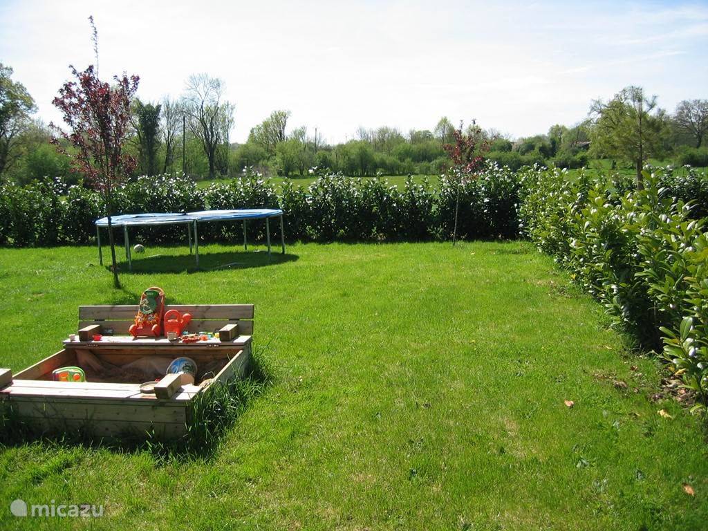 Tuin met trampoline en zandbak