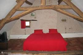 Spacious bedroom on first floor with beams and clay tiles (red french tiles) on the floor.