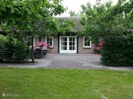 Vooraanzicht vakantiehuis met rozen in bloei en terras meubilair