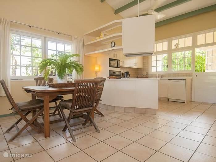 Ook binnen staat een eetkamertafel met bijbehorende stoelen. Grenzend aan de keuken.