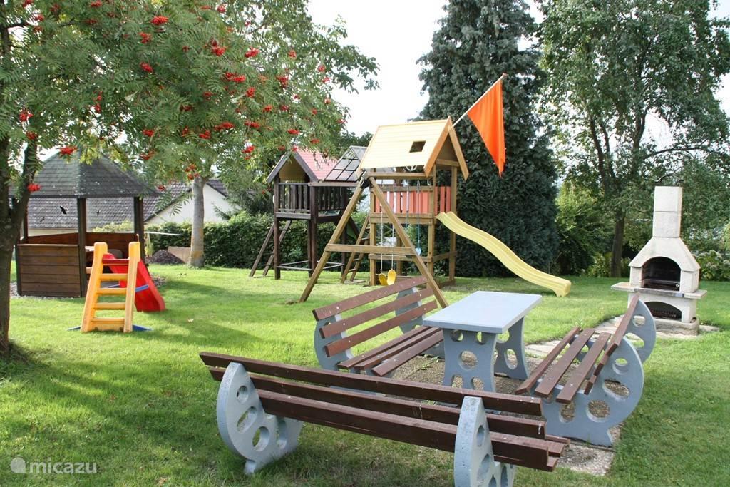 Tuin met speeltoestellen en barbeque