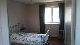 Slaapkamer met kastje en tafel en bed van 140x200.