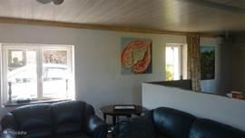 Gezellige woonkamer met satelliet tv,Haard zithoek uitkijkend op de tuin