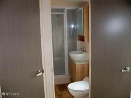 Badkamer met ruime douchecabine wastafel en toilet