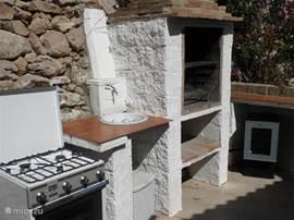 Buiten koken in de buitenkeuken, met barbecue, gaskookstel en koelkastje.