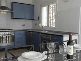 Ruime halfopen keuken met oven, vaatwasser, wasmachine en alle kookbenodigdheden.