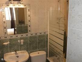 Ensuite badkamer 1 met bad / douche, grenzend aan slaapkamer 1.
