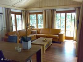 Riante woonkamer met schuifpui naar het aan de heide gelegen terras.