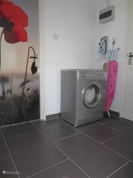 De washoek met strijkijzer, strijkplank en een wasmachine.