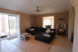 De woonkamer met openslaande deuren naar het terras en het zwembad.