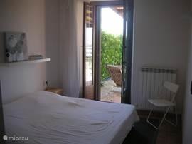 Grote slaapkamer met 2 eenpersoonsbedden (boxspring) en eigen badkamer + toilet. Openslaande deur naar terras, voorzien van schuifhor. Links van het bed is een grote hang- en legkast