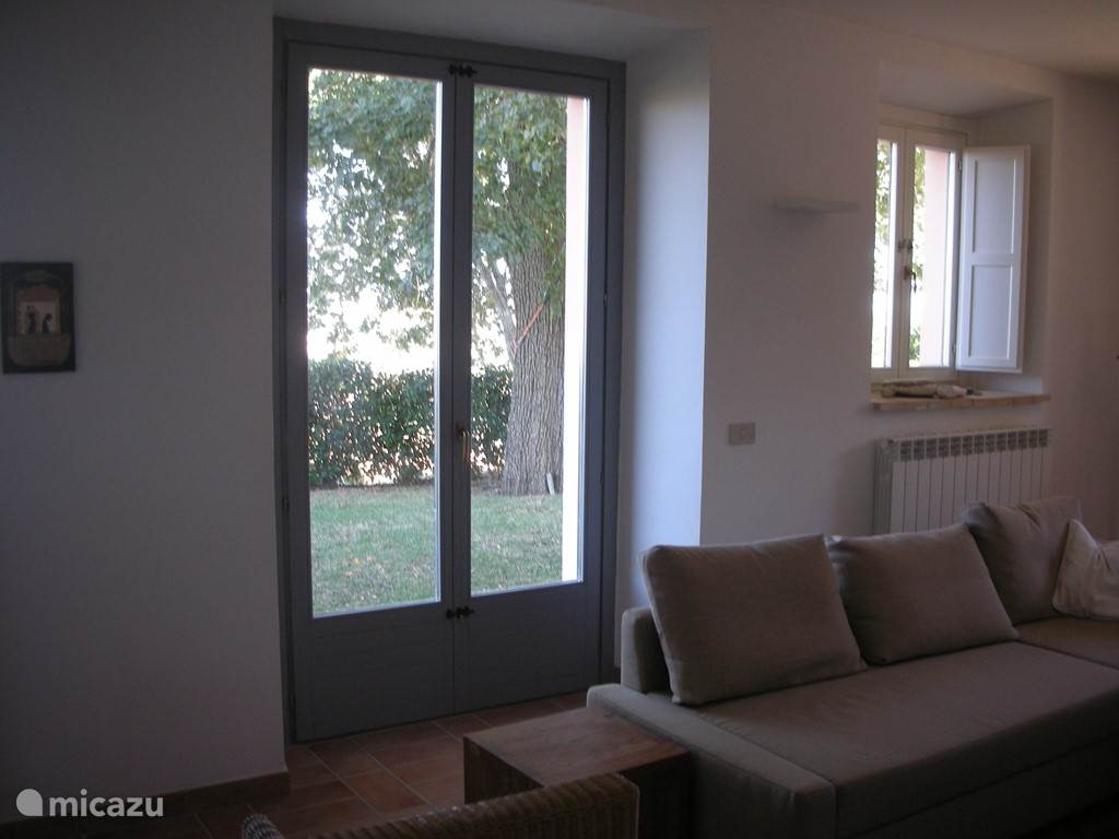 Grote openslaande deuren in woonkamer en woonkeuken, met zicht op landerijen en in de verte de Adriatische Zee.