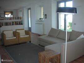 Modern ingerichte woonkamer met heerlijke bank, TV en haard..