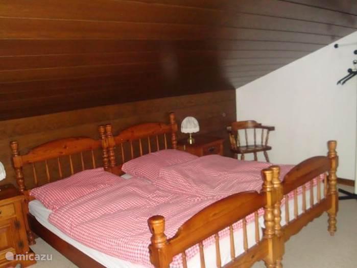 De grote slaapkamer op zolder met 2 grote 1 persoonsbedden.