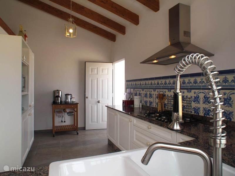 Een moderne keuken met de benodigde apparatuur. Een koelkast met eronder een vrieskast met laden. Onder de gaskookplaat met 5 pitten bevinden zich 2 brede lades met de borden en het bestek.