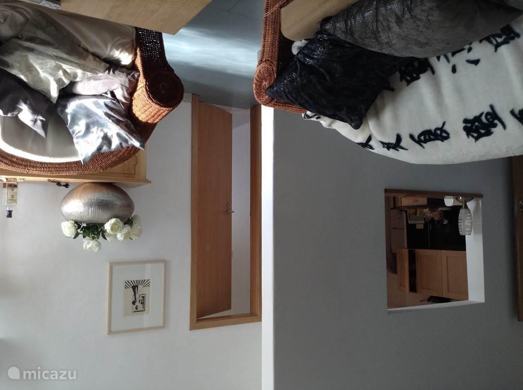Een overzicht vanuit de woonkamer met links een doorkijkje naar de keuken en rechts de deur naar de kleine badkamer en baby - kinderslaapkamer.