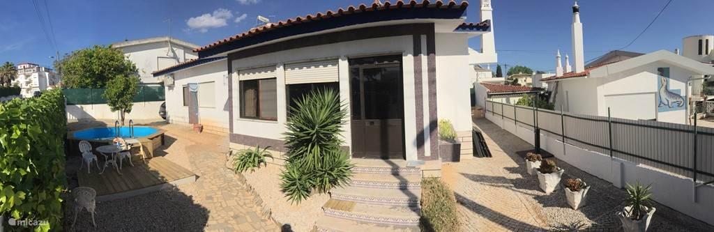 Overzicht van de gehele voorkant van de villa met links het zwembad met terrasje.