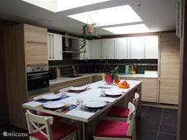 Sehr moderne Küche mit vielen Geräten. Sehr hell mit Blick auf den Garten