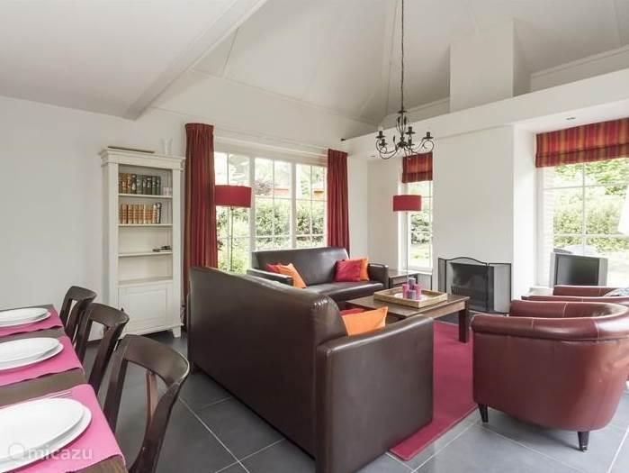 De sfeervolle woonkamer met vide en openhaard.