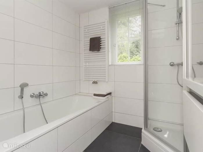De badkamer met ligbad, douche, grote wastafel met opberglade en design radiator.