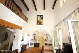 Eetkamer in de VILLA met hoog plafond en openslaande deuren naar de zijtuin met terras