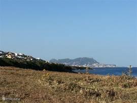 En als je bij de baaien omkijkt, kan je zien hoe dichtbij het dorp is. Je ziet het in de achtergrond. Het huis ligt daartussen. Verder op de achtergrond zie je overigens Gibraltar