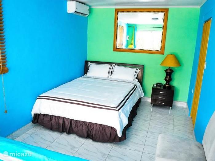 Bedroom with queen-size bed bedside table with lamp and alarm clock then one double bed also with bedside table and lamp room has ample closet and overlooks garden and pool.