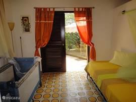 De tweede slaapkamer met airco en plafondfan heeft een 1 persoonsbed met onderschuifbed. Beide bedden vormen een volwaardig 2 persoonsbed. Er is voldoende ruimte voor een kinderbed. Deze slaapkamer heeft openslaande deuren naar de achtertuin met gazebo.