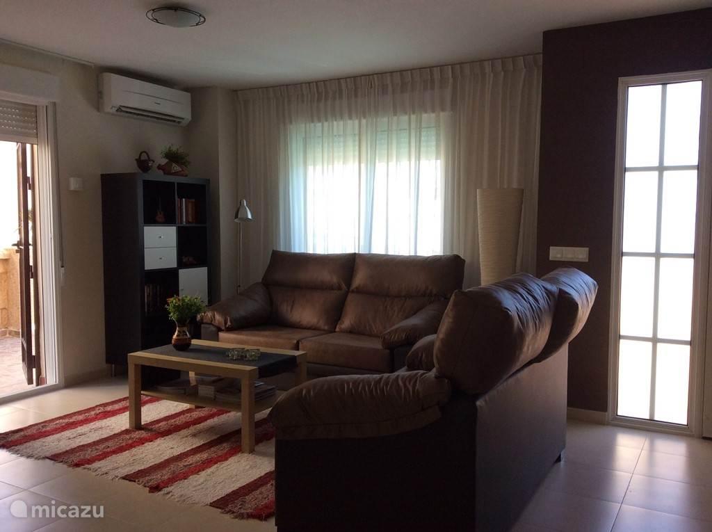 Ruime woonkamer met Nederlandse TV, Airco/verwarming. Diverse boeken (alle genres)