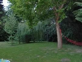 Een inkijkje in de tuin de hangmat hangt klaar voor gebruik