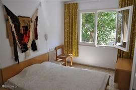Slaapkamer 1 met dubbel bed en mooi uitzicht op bomen.