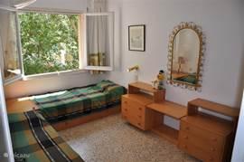 Slaapkamer met 2 persoonsbedden en zicht op de bomen.