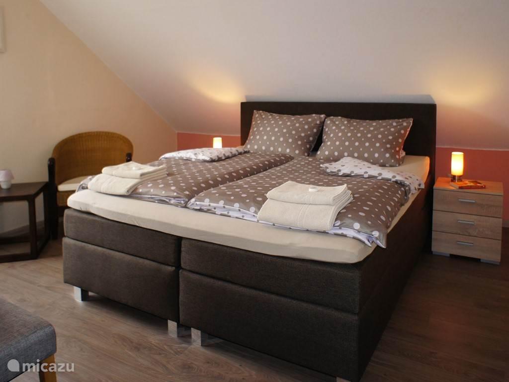 Slaapkamer met kingsize bed.