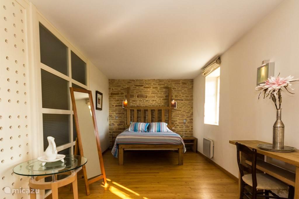 Ruime slaapkamer met eigen badkamer, voorzien van douche en bad.