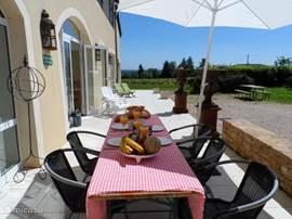 Voor het huis is een terras over de gehele breedte. Er staat een grote eettafel en er is een barbecue.
