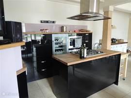 De open keuken ligt in de woonkamer. Een prachtige plek om gezamelijk te eten. De keuken is voorzien van alle moderne apparatuur.