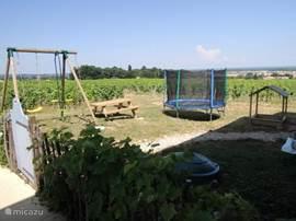 Naast het zwembad is een schommel en trampoline voor de kinderen.