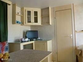 Opbergruimte en deur naar slaapkamer voor drie personen (met een stapelbed).