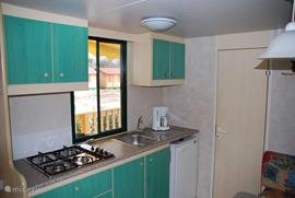 Keuken maakt deel uit van de woonkamer met uitzicht op veranda. De keuken is goed uitgerust.
