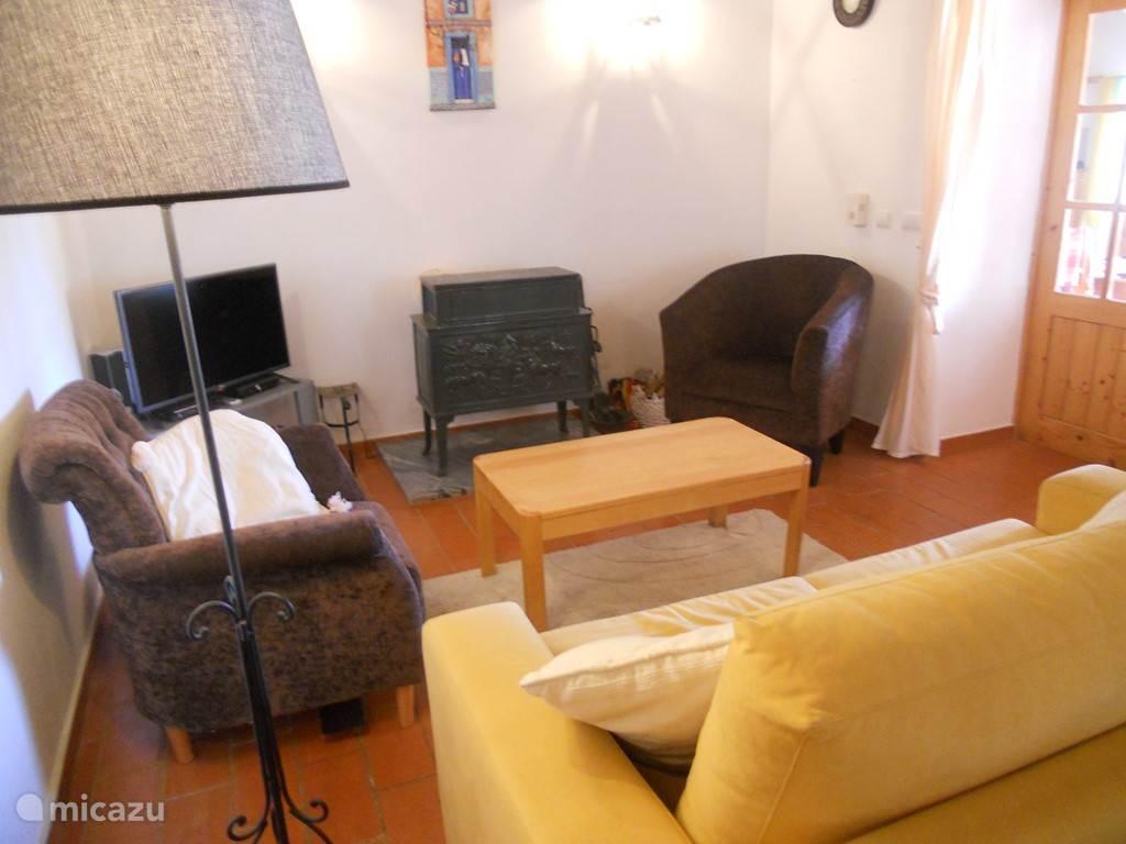 De zitkamer met houtkachel en televisie. Ontvangst van alle Nederlandse zenders en meer in HD kwaliteit.
