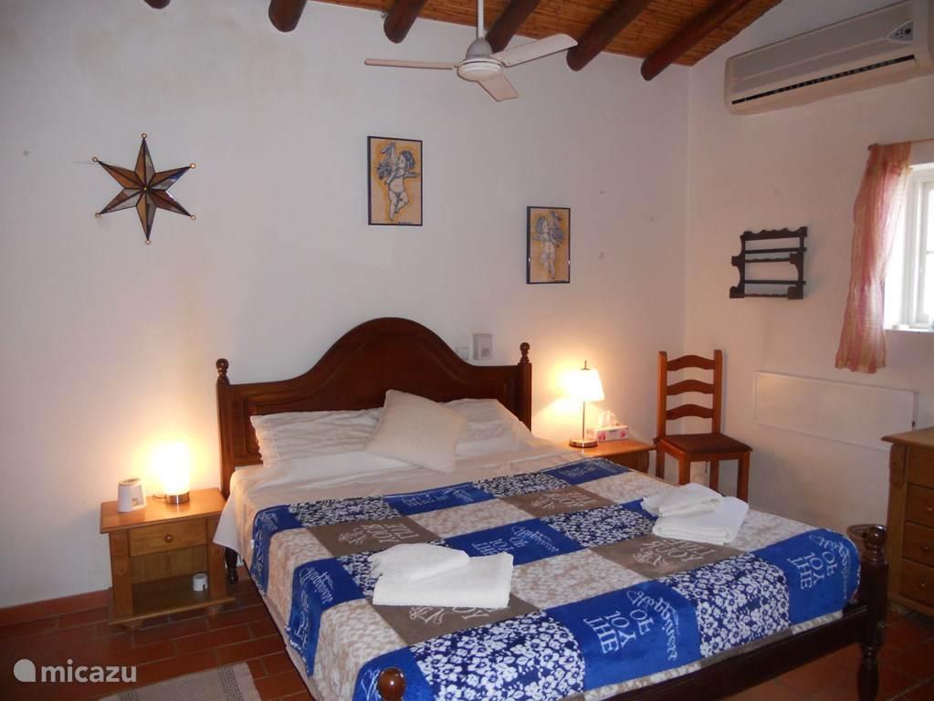 De ruime slaapkamer is voorzien van een royaal 2-persoonsbed, airconditioning en een plafondventilator. De kamer heeft een directe verbinding met de badkamer.