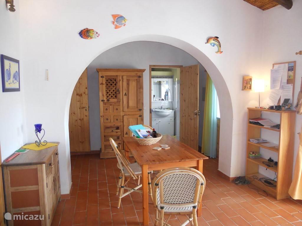 De eetkamer met links achterin de deur naar de slaapkamer en rechts achterin de deur naar de badkamer.
