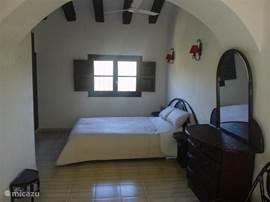 Een deel van de hoofdslaapkamer, balkenplafond en een boogvorm in he midden van de kamer. Met plafondventilator voor de verkoeling.