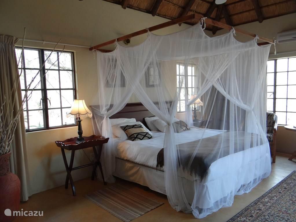 Hoofdslaapkamer met zitje, eigen badkamer en tuindeuren naar het terras met splashpool. De hoofdslaapkamer beschikt over airco, ventilatoren en een ruime en-suite badkamer.