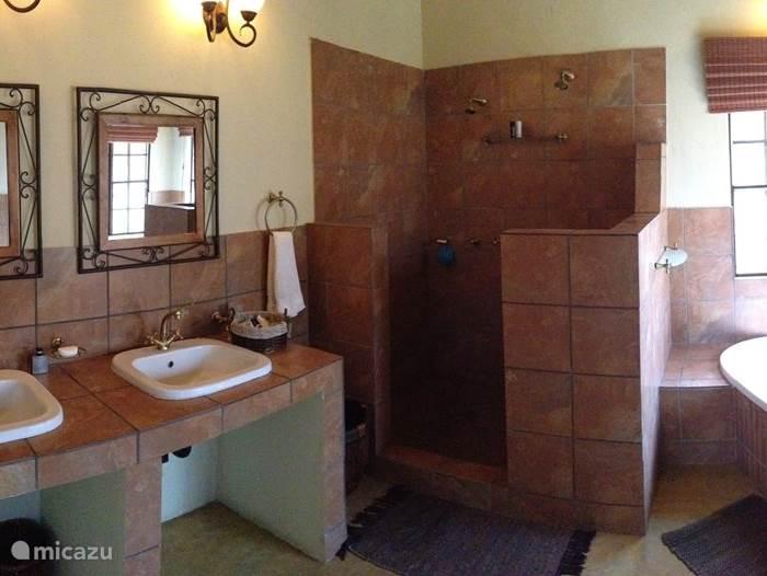 De hoofdbadkamer. Beide badkamers hebben dezelfde opzet.  Elke badkamer beschikt over een of twee wastafels, dubbele douche, ligbad en toilet. Het huis is volledig voorzien van handdoeken, linnengoed en dekbedden.
