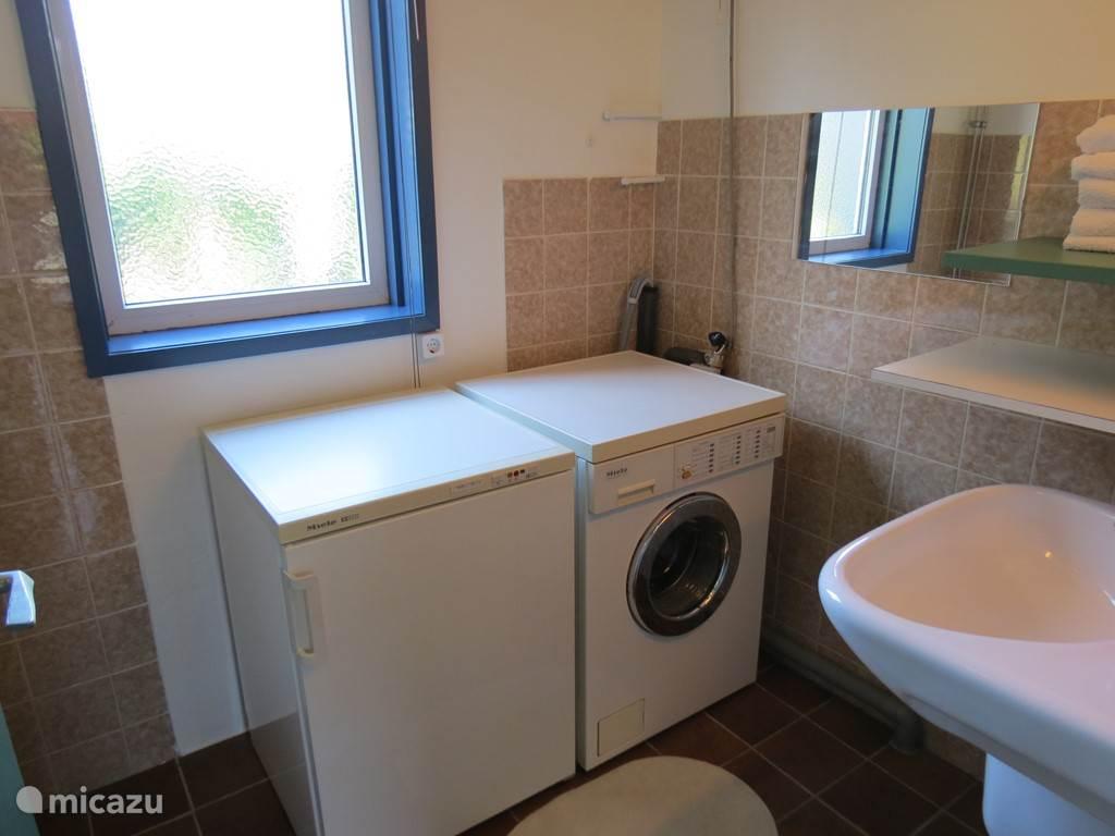 Wasruimte voorzien van wastafel, wasmachine en vriezer met laden.