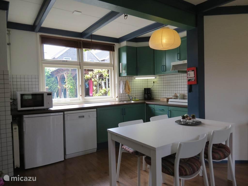 Heerlijke keuken met ruim aanrecht veel kastruimte, koelkast, vaatwasser en oven/magnetron.