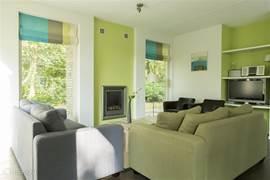 Moderne zithoek met tv-meubel en gashaard.
