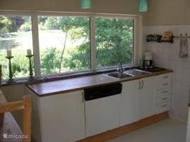 an open and bright kitchen with a beautiful view of nature. You can also pass the kitchen to the terrace.